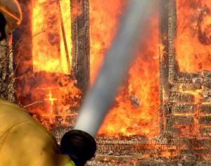 Feuerwehrmann läscht Brand mit Wasser.