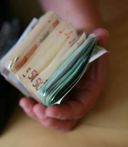 Hand voll mit Geldscheinen.