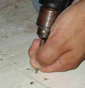 Mit der Bohrmaschine werden Löcher in ein Brett gebohrt.