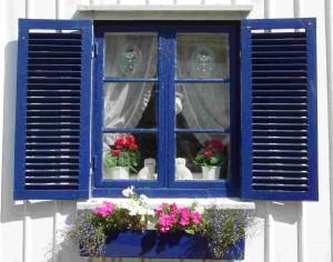 Weißes Haus mit blauen Fenstern.