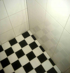 Schachbrettmuster auf dem Boden und große, helle Fliesen an der Wand.
