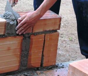 Handwerker baut eine Mauer aus Ziegeln.