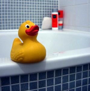 Gelbe Quietscheente auf Badewannenrand.
