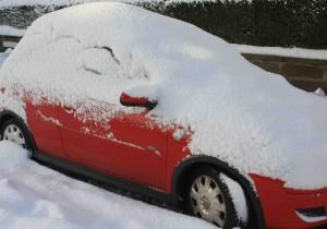 Ein mit Schnee bedecktes, rotes Auto.