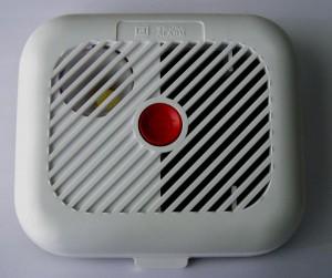 Weißer Brandmelder mit rotem Knopf.