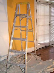 Leiter vor eine renovierungsbedürftigen Wand.