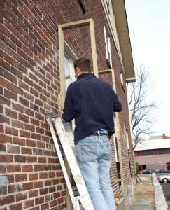 Mann repariert Fenster.