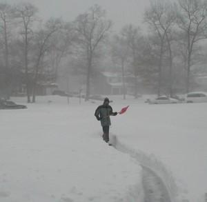 Mann schippt Schnee.