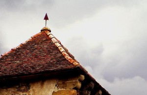 Beschädigtes Dach vor grauem Himmel.
