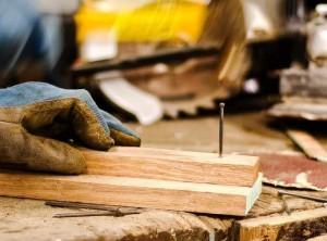 Handwerker schlägt einen Nagel in Bretter.