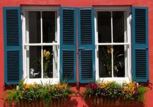 Rote Hausfassade mit weißen Fenstern und blauen Rolläden.