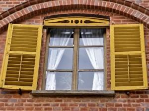Gelb lackiertes Holzfenster an einer Ziegelfassade.