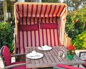 Gedeckter Tisch auf der Terrasse mit Stühlen und Strandkorb.
