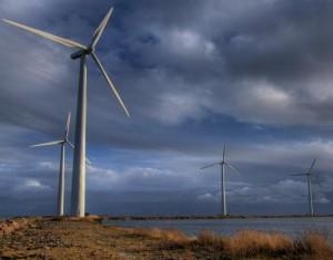 Windkraftwerke stehen am Wasser.