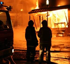 Feuerwehrmänner stehen vor einem brennenden Haus.