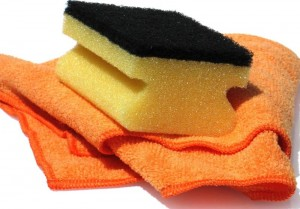 Gelber Schwamm liegt auf einem orangefarbenem Putzlappen.