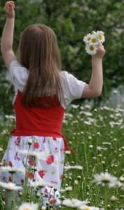 Kleines Mädchen mit Blumen in der Hand.