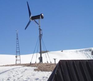 Ein kleines Windkraftwerk an einem Hang.