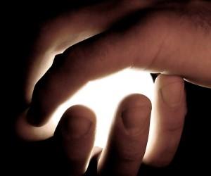 Hände umschließen eine Lichtquelle.