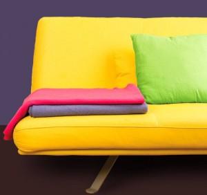 Gelbes Sofa mit bunten Kissen und Decken.