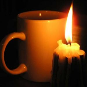 Tasse Tee mit brennender Kerze.