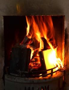 Offener Kamin mit brennendem Feuer.