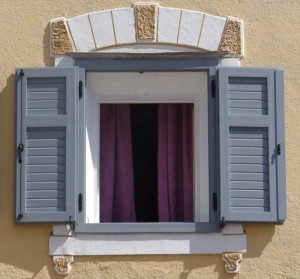 Holzfenster an einer hellen Fassade.