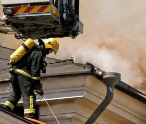 Ein Feuerwehrmann versucht auf dem Dach einen Brand zu löschen.