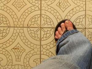 Fuß in Sandalen steht auf beigen Fliesen.