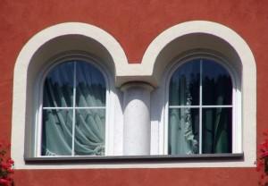 Weiße Kunststofffenster in roter Fassade.