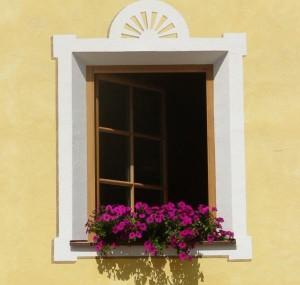 Gelbe Fassade mit einem mit Blumen geschmückten Fenster.