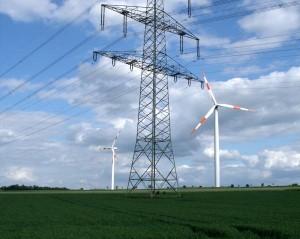 Ein Windkraftrad steht hinter einer Stromleitung.