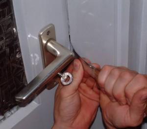 Einbrecher versucht eine Tür zu knacken.