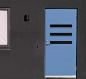Graue Hauswand mit moderner, baluer Tür.