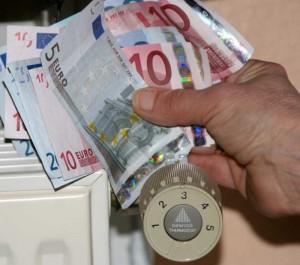 Eine Hand hält viele Geldscheine über ein Thermostat.