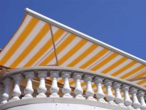 Gelb-weiß gestreifte Markise auf einem Balkon-