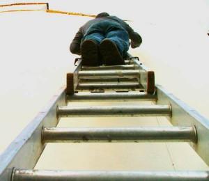 Mann steht auf Leiter.